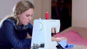 一位年轻裁缝缝合在一台缝纫机的衣裳 慢动作,照相机幻灯片权利 股票录像