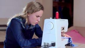 一位年轻裁缝缝合在一台缝纫机的衣裳 慢的行动 股票视频