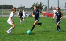 一位年轻足球运动员显示她的控球 库存图片