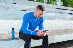 一位年轻运动员在立场坐并且听到音乐在训练以后 库存照片