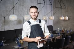 一位年轻,微笑的侍者在餐馆,站立在与一杯的桌旁边酒 穿戴在围裙,将接受命令 库存图片