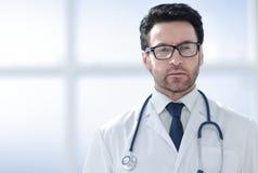 一位微笑的医生的画象在诊所的一间明亮的屋子 免版税库存照片