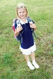 一位微笑的女小学生的画象一件蓝色学校礼服的 库存图片