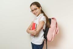 一位微笑的女小学生的画象与玻璃的10岁,与背包,笔记本 免版税库存图片