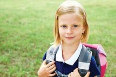 一位微笑的女小学生的画象一件蓝色学校礼服的 免版税库存图片