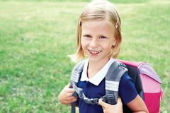 一位微笑的女小学生的画象一件蓝色学校礼服的 库存照片