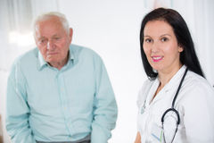 一位微笑的女性医生的画象有资深患者的在医疗办公室 免版税库存图片