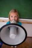 一位恼怒的女小学生叫喊通过扩音机 库存照片