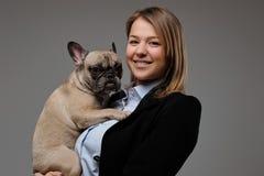 一位愉快的白肤金发的妇女交配动物者的画象拿着她逗人喜爱的哈巴狗 查出在灰色背景 免版税库存照片