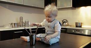 一位愉快的矮小的厨师厨师坐一张桌和戏剧与金属匙子,杯子 股票视频