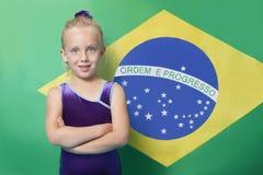 一位愉快的年轻女性体操运动员的画象有胳膊的横渡了在巴西旗子前面的身分 免版税图库摄影