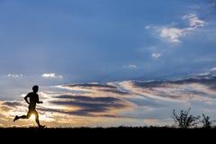 一位慢跑者的剪影在日出的 库存照片