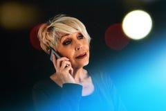 一位成功的正面年长女性顾问谈判手机 人使用之间的通信现代 免版税库存图片
