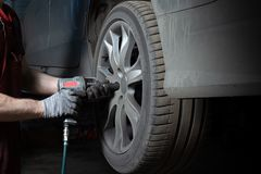 一位技工在服务中心检查汽车的停止 执行季节性轮子替换 免版税图库摄影