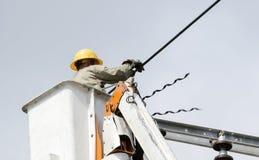一位技术员在一根电杆安装新的缆绳从 库存照片
