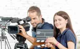 一位摄影师和一个少妇有电影摄影机和拍板的 免版税库存图片