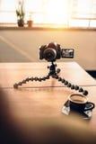 一位摄影师的书桌用咖啡和三脚架登上了数字式加州 免版税库存图片