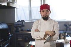 一位时兴的厨师的画象拿着一把刀子的班丹纳花绸的在厨房里 免版税库存照片