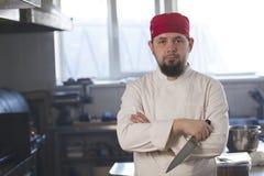 一位时兴的厨师的画象拿着一把刀子的班丹纳花绸的在厨房里 库存图片