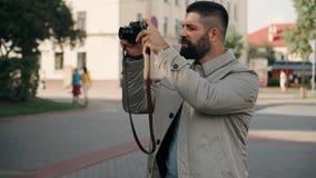 一位有胡子的旅游人摄影师步行街道和照片 时髦地穿戴的式样慢动作 股票录像