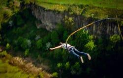 一位极端运动员在从了不起的高度的一条绳索跳 库存图片