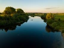 一位渔夫的剪影一条小船的在日落的一条河 库存照片