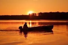 一位渔夫的剪影一条小船的在河,黎明 库存图片