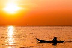 一位渔夫的剪影一条小船的在海 免版税库存照片