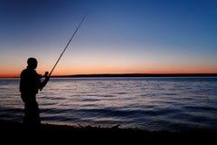 一位渔夫的剪影有一根钓鱼竿的在美好的日落 反对山 免版税库存图片