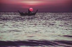 一位渔夫的剪影木小船的在日落 库存图片