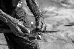 一位渔夫的手有刀子的 免版税库存照片