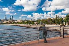 一位渔夫的铜雕塑码头的 库存图片