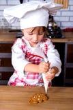 一位烹调厨师的帽子的逗人喜爱的女孩装饰有甜结冰的现成的被烘烤的姜饼圣诞树小雕象和 库存图片
