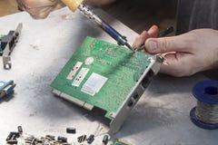 一位焊接的战士的手有焊铁的 免版税库存图片
