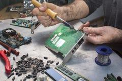 一位焊接的战士的手有焊铁的 库存图片