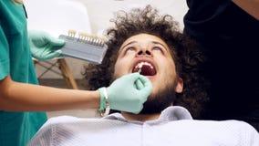 一位牙医的英尺长度有她的检查牙颜色的一片年轻manÂ的树荫助理的 股票视频