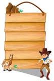 一位牛仔和一头驴在空的牌前面 免版税库存图片