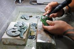 一位玉装饰绿色岩石雕刻师的手在工作 库存照片