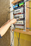 一位电工的手有螺丝刀的在一个电子互换机内阁 免版税库存图片