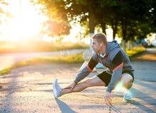 一位男性教练在训练揉他的腿与耳机前 赛跑者早晨在公园 听音乐 免版税库存照片