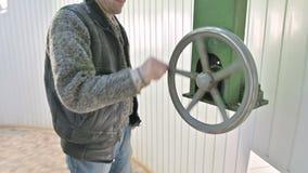 一位男性研究员转动太阳观测所的圆顶门的打开的机制的手工轮子 ?? 股票录像