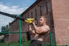 一位男性运动员参与露天圈,训练二头肌 在夏天,简而言之和光秃的躯干 健康生活方式 库存照片