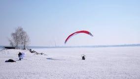 一位男性运动员横跨在一个滑翔伞的天空在雪飞行,在冬天,做着陆 4K 3840x2160 股票视频