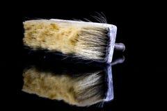 一位画家的一把油漆刷在玻璃桌上 绘画accessorie 免版税库存图片