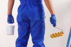 一位画家,举行建筑路辗和一个罐头的腿制服和手套的油漆 免版税库存图片
