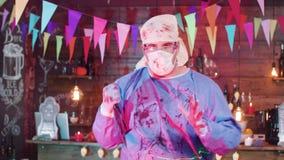 一位疯狂的精神分析的医生的万圣节服装有一把血淋淋的刀子的在他的手上 股票录像