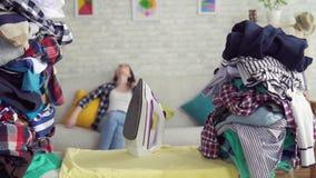一位疲乏的妇女主妇的画象堆背景的衣裳 股票录像