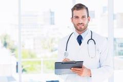 一位确信的男性医生的画象有剪贴板的 图库摄影