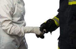 一位科学家和消防员的握手白色防护套服的 免版税库存图片