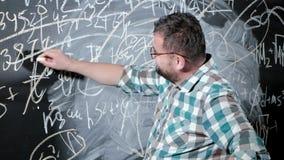 一位精采成熟数学家带来一个大块板并且完成杂文复杂的数学公式等式 影视素材